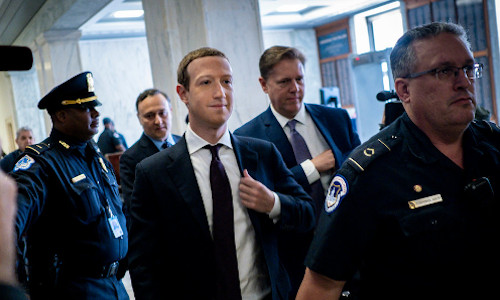 Facebook founder Mark Zuckerberg surrounded by guards.